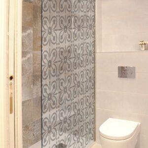 sticker petits pétales collé sur une porte de douche dans une petite salle de bain