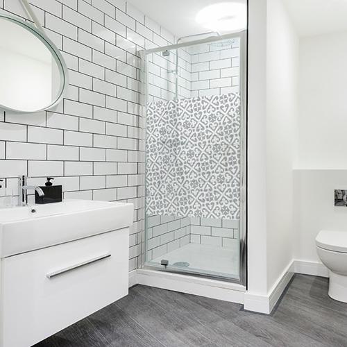 Sticker format carré avec des petits motifs Moyen Orient en diagonale posé sur une porte dans une salle de bain moderne et éclairée