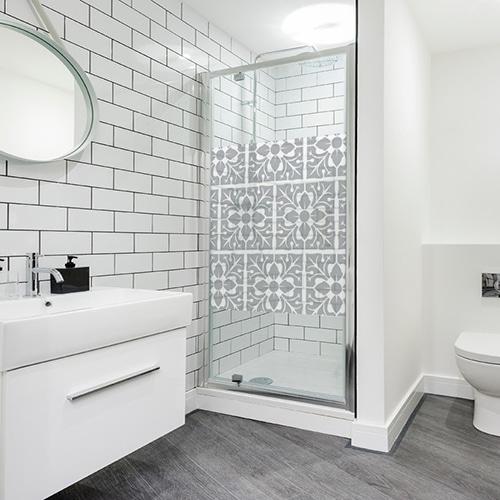 sticker carré motif feuille collé sur une porte de douche dans une salle de bain moderne