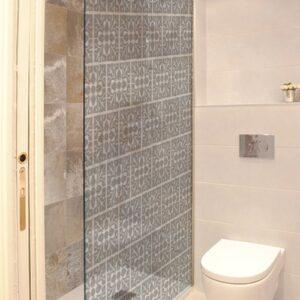 sticker petit motif feuille collé sur la porte de douche d'une petite salle de bain