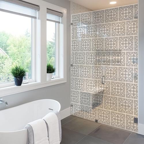sticker adhésif petit motif feuille collé sur une porte de douche dans une salle de bain de luxe équipée d'une baignoire
