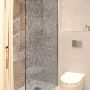 Sticker motif rond collé sur une vitre de douche dans une petite salle de bain avec WC