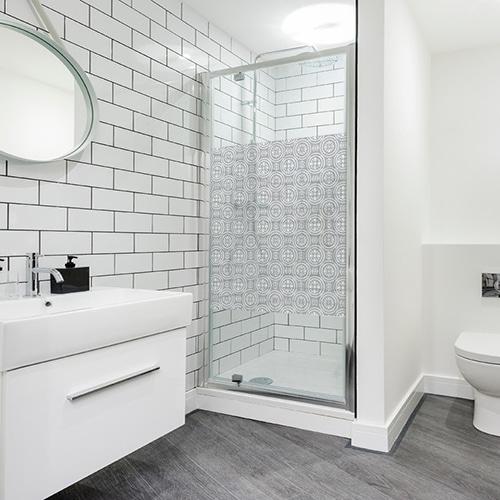 Sticker autocollant motif rond collé sur une vitre de douche dans une salle de bain moderne et éclairée