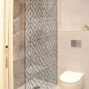 Sticker motif losange noir et blanc collé sur une vitre de douche dans une petite salle de bain