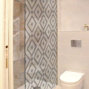 sticker style méditerranéen collé sur une vitre de douche dans une petite salle de bain avec WC