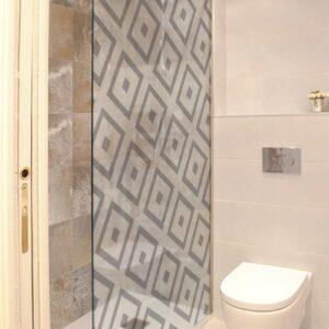sticker décoratif autocollant motifs losanges d'inspiration méditérranéenne collé sur la vitre d'une douche dans une petite salle de bain