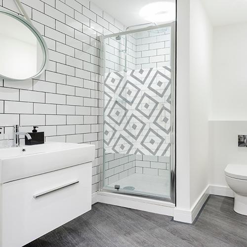 sticker décoratif autocollant motifs losanges d'inspiration méditérranéenne posée sur la porte d'une douche moderne