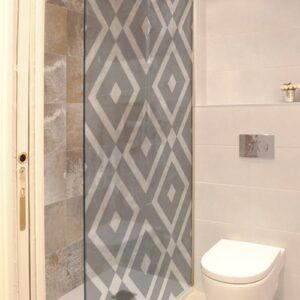 Sticker décoratif adhésif losange noir et transparent collé sur la vitre de la douche d'une petite salle de bain