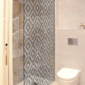 sticker décoratif adhésif motif méditerranéen collé à la porte d'une douche dans une petite salle de bain