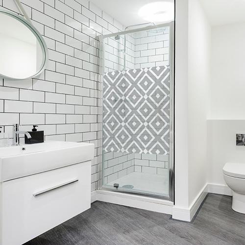 sticker décoratif adhésif motif méditerranéen en carré collé à la vitre d'une salle de douche moderne et éclairée