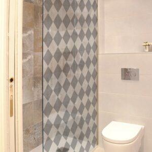 sticker décoratif adhésif motif damier gris et blanc collé à la vitre d'une petite salle de douche avec toilettes