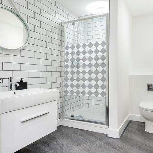 sticker décoratif adhésif motif damier gris et blanc format carré collé sur la vitre d'une douche moderne dans une salle de bain éclairée et lumineuse