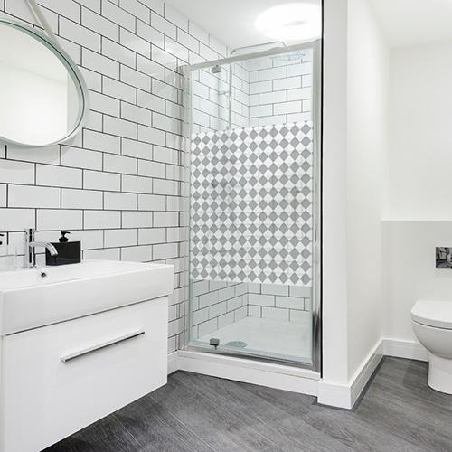 Sticker adhésif décoratif motif petits damiers gris et blanc au format carré dans une salle de bain moderne et lumineuse