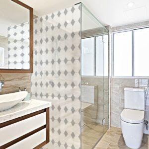 Sticker décoratifs motif vichy petit losanges gris collé sur la porte vitrée d'une petite salle de bain