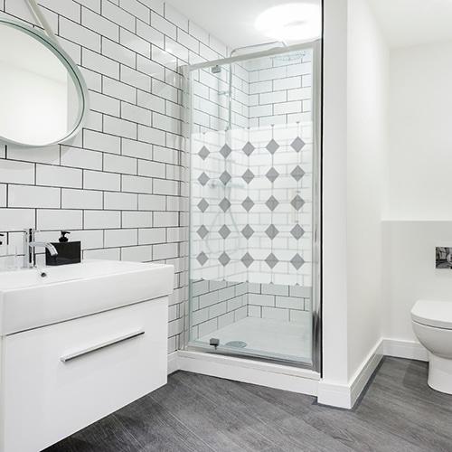 Sticker autocollant décoratif grand losanges gris motifs Vichy collé à la porte vitrée d'une salle de bain lumineuse et moderne blanche