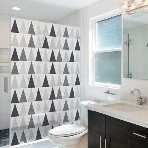 sticker décoratif autocollant motif triangles noirs blanc et gris collé sur la vitre de la douche d'une petite salle de bain