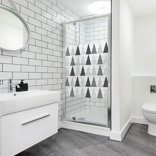 sticker format carré décoratif autocolnt motif triangles noirs blanc et gris collé sur la porte vitrée de la douche d'une salle de bain blanche et moderne (avec WC)
