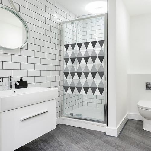 Sticker décoratif au format carré Motifs losanges gris et noirs collé sur la porte de douche d'une salle de bain blanche et lumineuse