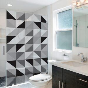 Sticker décoratif autocollant motif triangles noirs, blancs et gris collé sur une baignoire douche dans une petite salle de bain