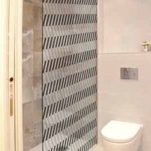 Sticker adhésif décoratif motif chevrons horizontaux chevrons blanc et noirs collé sur la vitre d'une petite douche dans une petite salle de bain avec WC