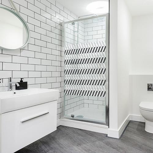 Sticker format carré adhésif motif chevrons horizontaux blanc et noirs collé à la porte de la douche d'une salle de bain éclairée et moderne