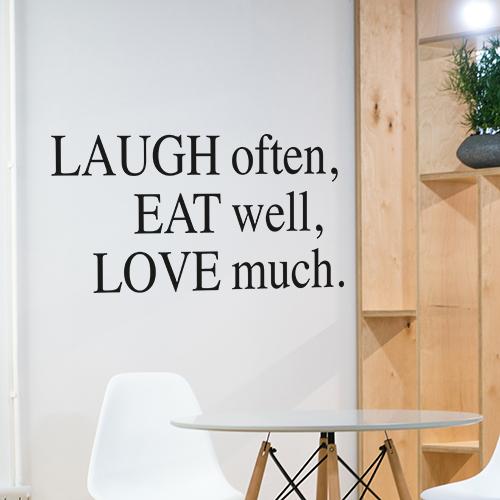 Sticker mural Laugh Often décoration à côté d'une étagère dans une pièce à vivre