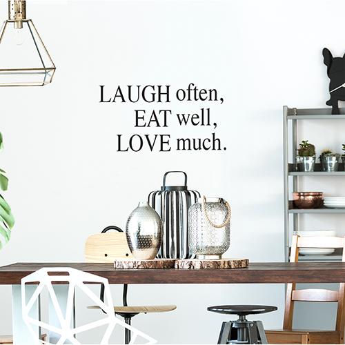 Sticker adhésif Laugh Often au dessus d'une table dans le salon