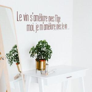 Sticker mural citation Le vin s'améliore dans un salon à côté d'une plante et d'un miroir