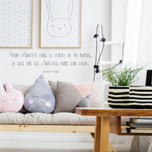 Pièce à vivre avec un sticker citation ventre de ma maman collé au mur au dessus du canapé
