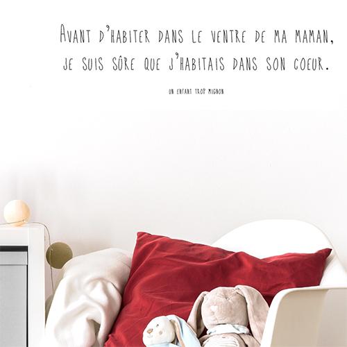 Chambre de petite fille avec un sticker VENTRE DE MA MAMAN collé au mur