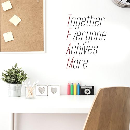 Bureau moderne avec un sticker citation définition TEAM collé au mur