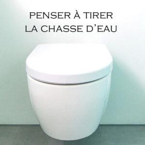 Toilettes blancs avec un sticker adhésif instruction Penser à tirer la chasse d'eau au mur