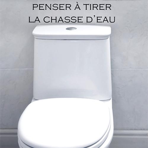 Salle de WC grise moderne avec un sticker citation Penser à tirer la chasse d'eau collé au mur