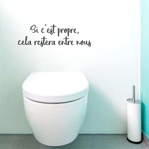 Toilettes blanches avec un sticker déco citation si c'est propre collé au mur