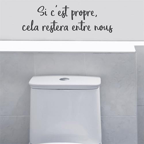 Salle de WC moderne avec un sticker Si c'est propre collé au mur