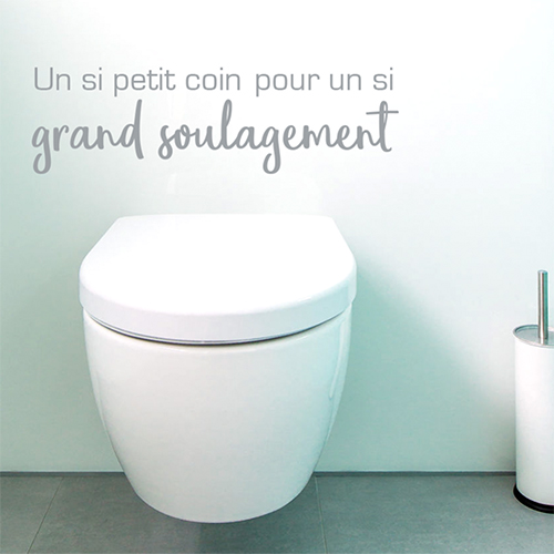Toilettes blanches surplombées d'un sticker citation un si petit coin