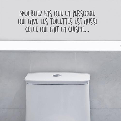 Salle de WC avec un sticker citation personne qui lave les toilettes