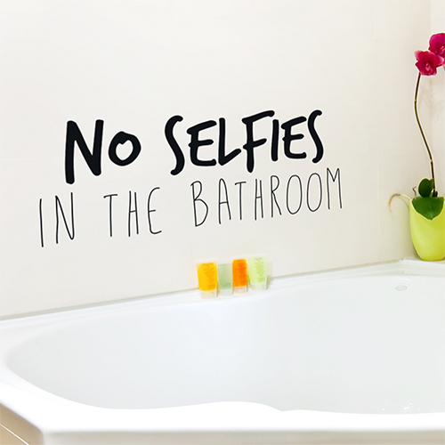 Baignoire moderne surplombée d'un sticker citation No selfies in the bathroom