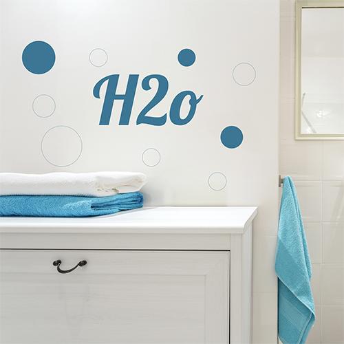 Sticker adhésif citation H20 collé près du mirroir dans une salle de douche