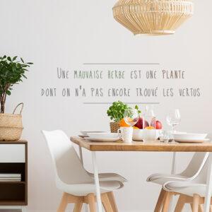 Citation Mauvaise Herbe adhésive collée au mur d'une pièce à vivre.