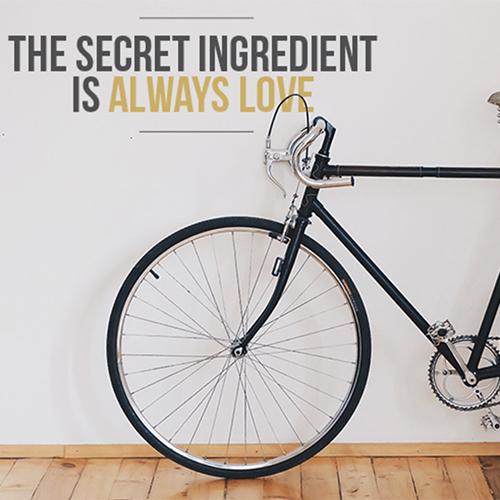 Couloir de l'entrée avec un vélo et un sticker citation the secret ingredient is always love