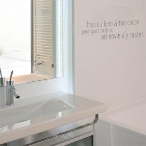 Sticker citation bien-être fais du bien à ton corps collé près du miroir d'une salle de bain
