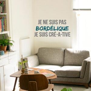 Sticker mural Je ne suis pas bordélique au dessus d'un fauteuil dans un salon