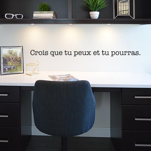 Sticker citation Crois que tu peux posé sur le mur au dessus d'un bureau noir moderne