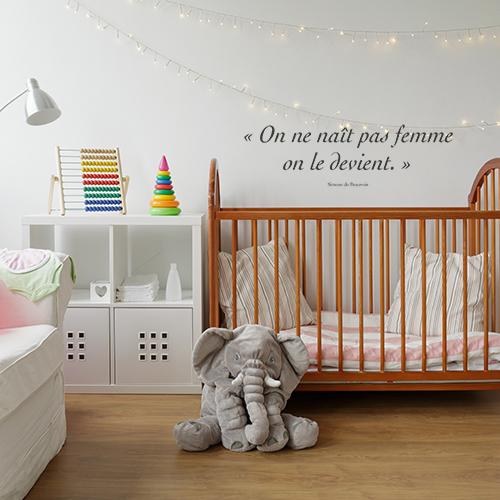Sticker On ne nait pas femme citation au dessus d'un lit de bébé