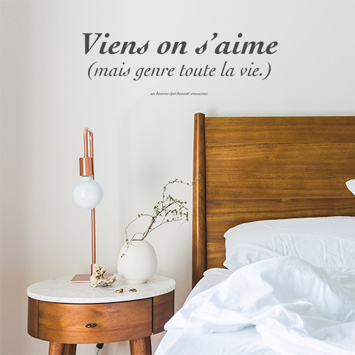 Sticker adhésif Vient on s'aime citation posée au dessus d'une tête de lit avec une lampe