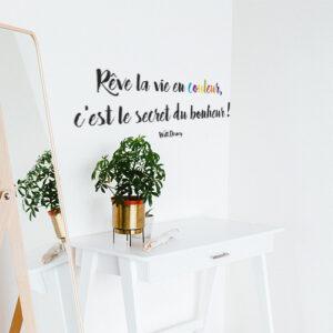 """Sticker autocollant """"rêves la vie en couleur, c'est le secret du bonheur"""" collé au mur au dessus d'une table"""