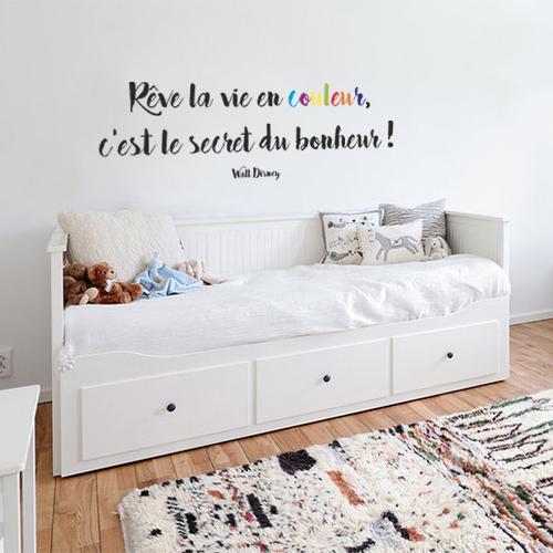 """Sticker adhésif """"rêves la vie en couleur, c'est le secret du bonheur"""" collé au mur au dessus d'un lit d'enfant"""