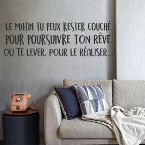 """Sticker """"le matin tu peux rester couché pour poursuivre ton rêve ou te lever pour le réaliser"""" collé sur un mur de salon cosy"""