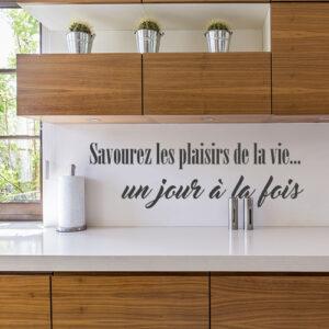 Sticker citation pour cuisine savourez les plaisirs collé au mur d'une cuisine